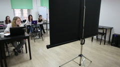 Projection screen is on center of room for audience at lesson - stock footage