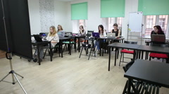 Seminar of pen and tablet creativity with students and teacher sitting at desks - stock footage