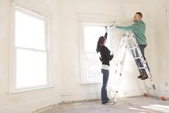 Mixed race couple installing shade in new home Stock Photos