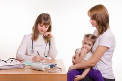 Pediatrician writes appointment for treatment sick child - stock photo