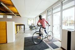 Blurred view of businessman pushing bicycle into office Stock Photos