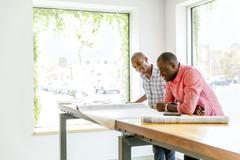 Businessmen reading blueprints in office Stock Photos