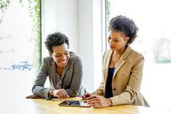 Businesswomen using digital tablet in office Stock Photos