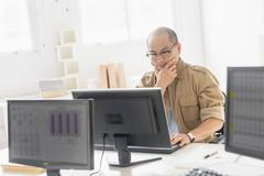 Korean businessman working on computer at office desk Stock Photos