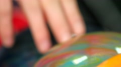 Hand taking multicolored ball from bowling ballmachine. Сamera moves the bottom Stock Footage