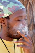 Rastafarian smoking marijuana - stock photo
