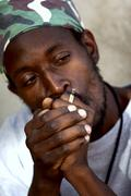 Rastafarian man smoking marijuana - stock photo