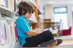 Mixed race student writing in notepad on floor in library Stock Photos