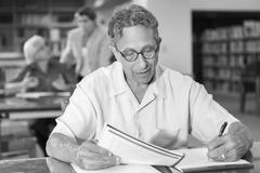 Caucasian man writing on notepad in library Stock Photos