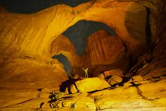 Hiker standing in illuminated rocks at night in Arches National Park, Moab, Stock Photos