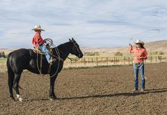 Caucasian woman teaching boy to use lasso on ranch Stock Photos