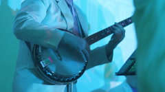 Man in white suit playing on banjo in discolights Stock Footage