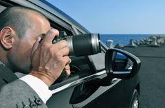 detective or paparazzi taking photos from inside a car - stock photo
