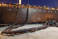 Oil tanker ship docked in industrial harbor Stock Photos