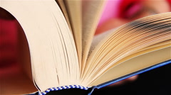 Woman turns book's pages Stock Footage