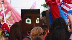 Zanqueros and big head characters in the middle of crowd at festival Stock Footage