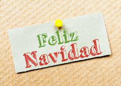 Recycled paper note pinned on cork board. Feliz Navidad Message. Concept Imag Stock Photos