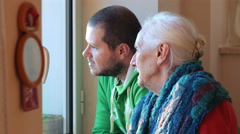 Grandmother and grandson talking: elderly woman search comfort with old memories - stock footage