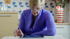 Elderly woman using tablet computer on the table in her kitchen Stock Footage