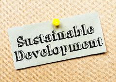 Recycled paper note pinned on cork board. Sustainable Development Message - stock photo