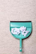 Green dustpan for house work with garbage papers on floor indoors. Cleaning Stock Photos