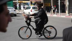 Man on bicycle in the main street during Purim Stock Footage