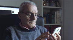 Stock Video Footage of thoughtful old man is using smartphone with touchscreen