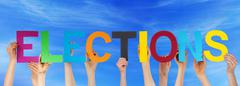 Stock Photo of Many People Hands Holding Colorful Straight Word Elections Blue Sky