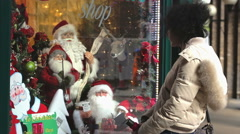 Woman looks at the windows of a shop during christmas time Stock Footage