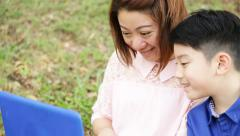 Happy asian mother and child playing on laptop computer in garden . Stock Footage