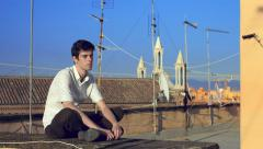 Pensive young man sitting on the roof of a building Stock Footage