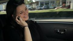 business woman sitting back in the car having successful news on phone - stock footage