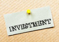 Investment word written on paper note - stock photo