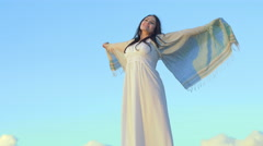 Beautiful woman opens arms like an angel with sky in background Stock Footage