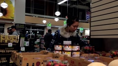 Woman selecting strawberry in grocery store - stock footage