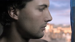 sad and pensive young man looking out of the window: lateral portrait - stock footage