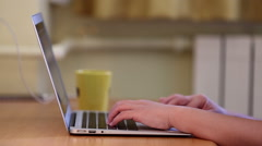 browsing website on laptop while drinking coffee or tea - stock footage