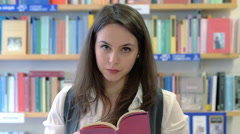 smiling student woman reading a new book in the bookshop  - stock footage