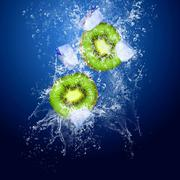 Water drops around kiwi on blue background - stock photo
