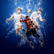Water drops around football players under water on blue background - stock photo