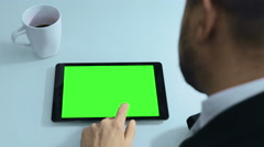 Man working with tablet computer with green screen on display Stock Footage