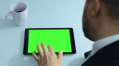 Man using tablet computer sitting on the table with coffee cup: green screen Stock Footage