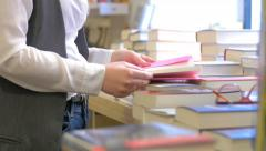 young woman searching for a book in a bookshop - stock footage