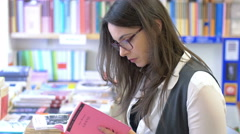 bookshop: cute young woman reading surrounded by the shelves of the bookstore - stock footage