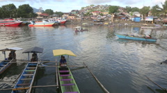 Wooden outrigger water taxi boats on Manado River Stock Footage
