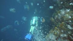 Oxygen bubbles from female scuba diver rising to the ocean surface Stock Footage