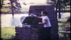 1855 - young boy barbecues by the lake on summer day - vintage film home movie Stock Footage