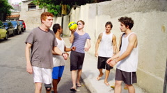 Young Brazilian men throw a soccer ball around outside Stock Footage