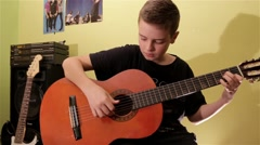 Teenage Boy Playing Acoustic Guitar In His Room Fingerstyle Stock Footage
