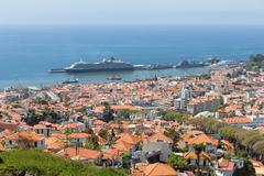 Aerial view of Portugese Funchal with a big cruise ship in the harbor - stock photo